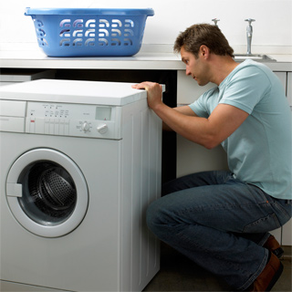 Man examining back of washer